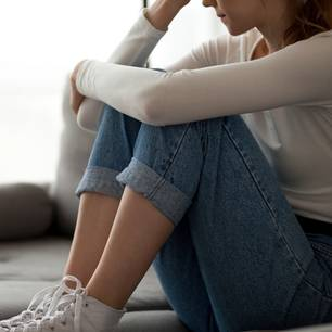 Schlechtes Gewissen: Frau grübelt auf dem Boden
