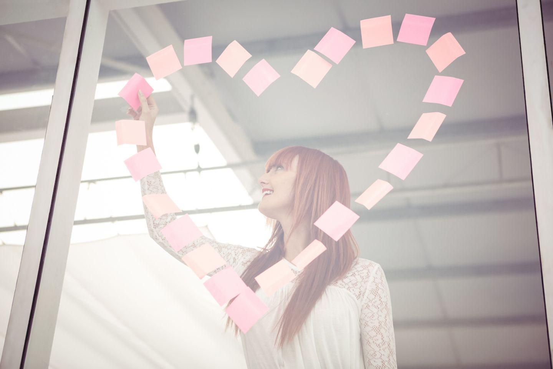 Liebe am Arbeitsplatz: Frau die mit Post-Its ein Herz an die Scheibe klebt