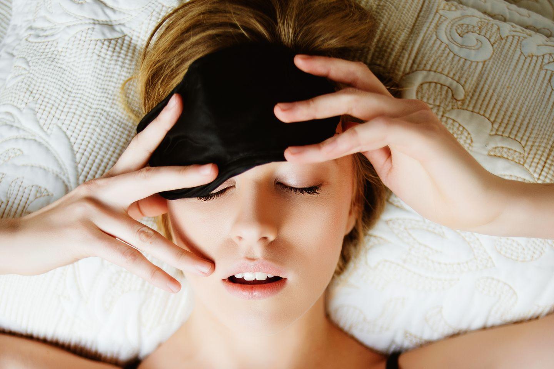 Geschwollene Augen: Frau mit Schlafmaske im Bett