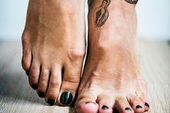 Tattoo am Fuß: Zwei Frauenfüße mit Schlangentattoo