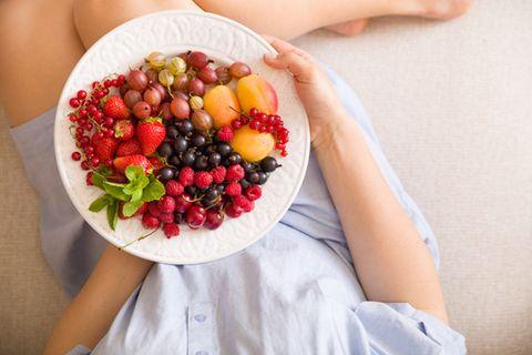 Fructoseintoleranz: Was darf ich essen? Frau hält einen Teller mit verschiedenen Obstsorten in der Hand