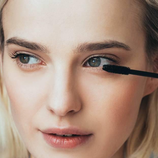Schminken mit Kontaktlinsen: Frau tuscht sich die Wimpern