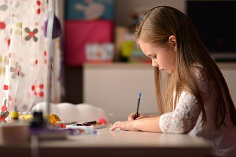 Junges Mädchen schreibt Schul-Aufsatz