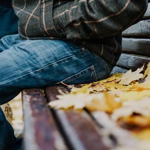 Benching: Ein Mann sitzt allein auf einer Parkbank
