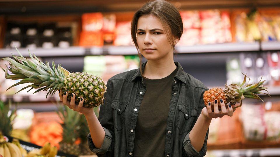 Junge Frau hält im Supermarkt skeptisch eine Ananas hoch