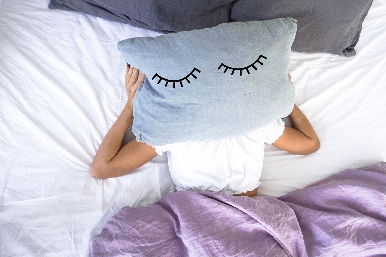 Augenschatten: Frau liegt im Bett und hält Kissen über dem Kopf