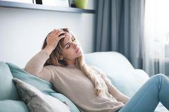 Müdigkeit: Müde Frau sitzt auf dem Sofa