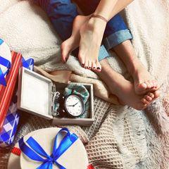 Valentinstagsgeschenke für Männer: Paar auf der Couch mit Geschenken