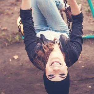 Kleinkind-Strategie: Fröhliche Frau kopfüber auf einer Schaukel