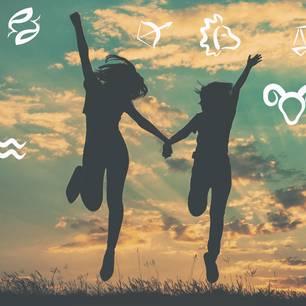 4 Gründe, warum Widder unser Leben bereichern: Zwei fröhliche Frauen springen in der Dämmerung