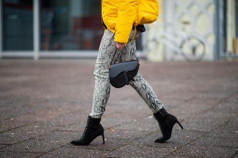 Berlin Fashion Week: Frau mit schwarzen Stiefeletten, Schlangen-Hose und gelber Jacke