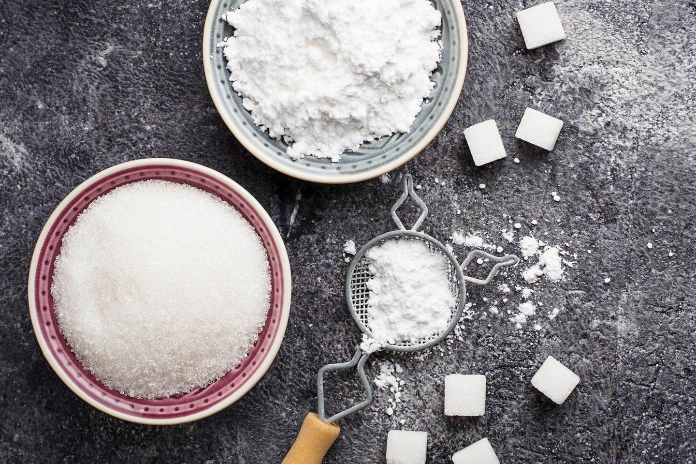 Puderzucker selber machen – in wenigen Schritten: Eine Schale mit Zucker und eine mit Puderzucker auf dem Tisch.