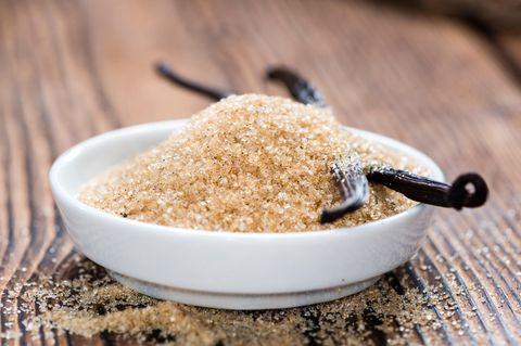 Vanillezucker selber machen – schnell und einfach: Eine Schale mit braunem Zucker und zwei Vanilleschoten steht auf dem Tisch