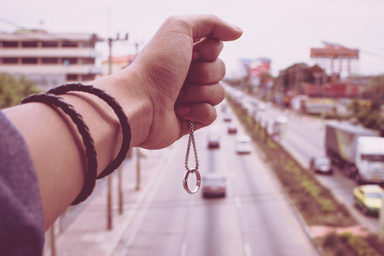 Typische Trennungsgründe, die keine sind: Frauenhand hält Ehering an einer Kette über eine 6-spurige Straße