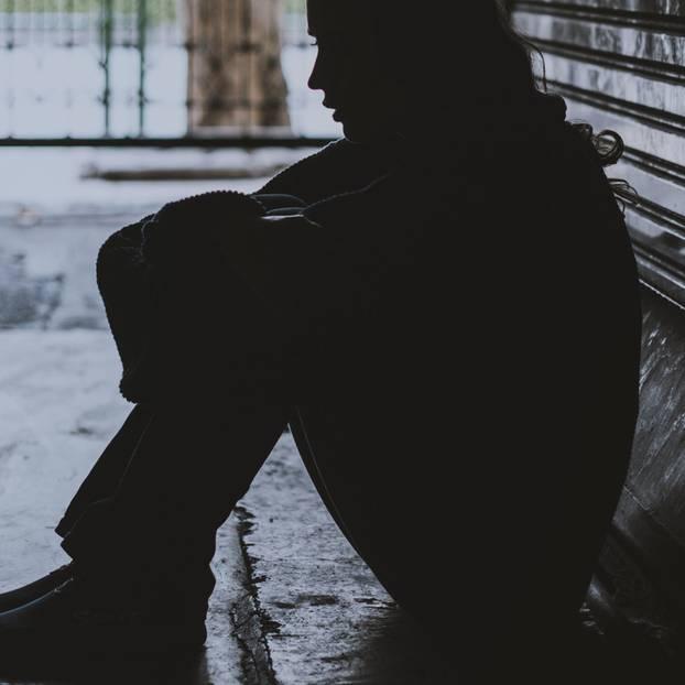 Obdachlos - und keiner weiß es: Frau sitzt im Schatten auf der Straße
