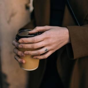 Tattoo am Finger: Eine Frau mit Finger-Tattoo und Kaffeebecher in der Hand