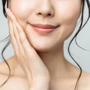 Periorale Dermatitis: Frau, die sich mit Hand an Wange fasst