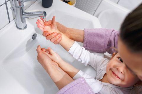 Erkältung: Mutter wäscht mit Kind die Hände