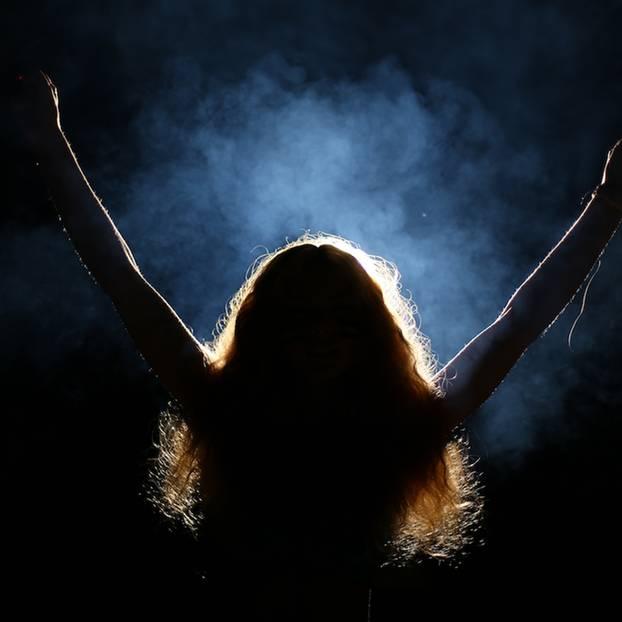 Drogen, Alkohol, Party - Mutter geht heimlich feiern: Frau von hinten, im Scheinwerferlicht