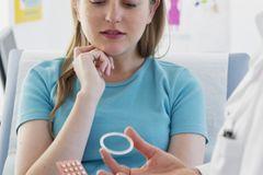 Verhütungsring – das solltest du wissen: Frau im Gespräch mit einem Arzt, der Pille und Verhütungsring in der Hand hält