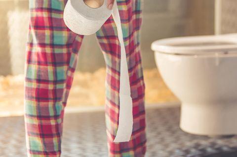 Verstopfung: Frau steht vor der Toilette