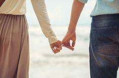 Dieses Wort gefährdet Beziehungen: Mann und Frau halten mit den kleinen Fingern Händchen am Strand