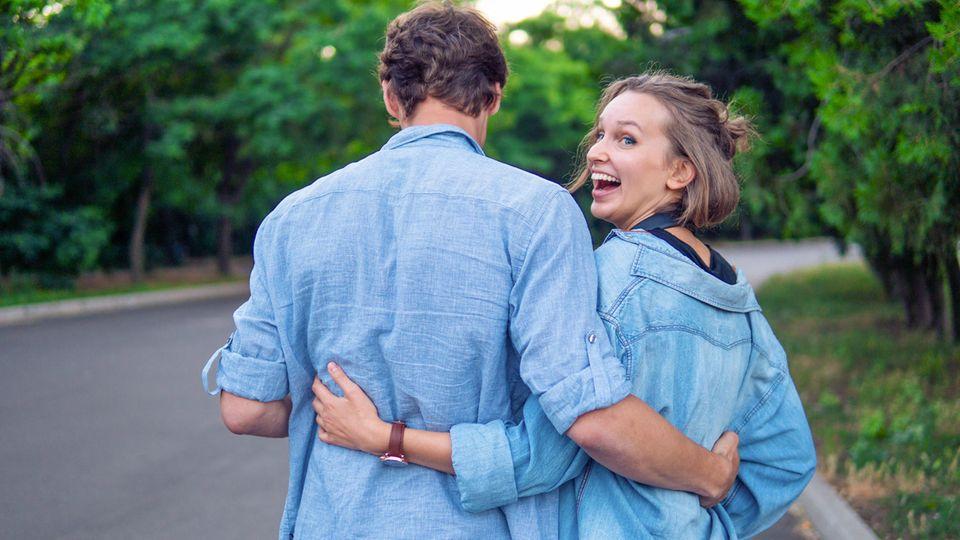 ElitePartner: Ein Pärchen im Partner-Jeans-Hemd-Look von hinten