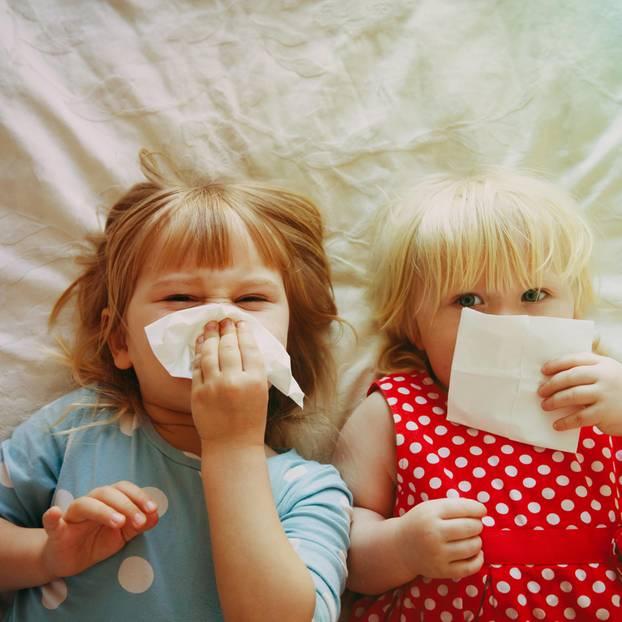Nase putzen lernen: zwei Kinder mit Taschentüchern auf Bett liegend