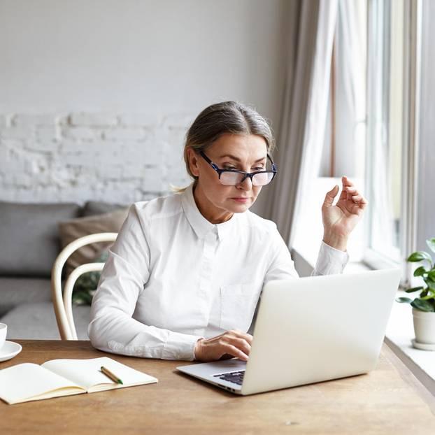 Rente beziehen und Vollzeit arbeiten: Ältere Frau am PC