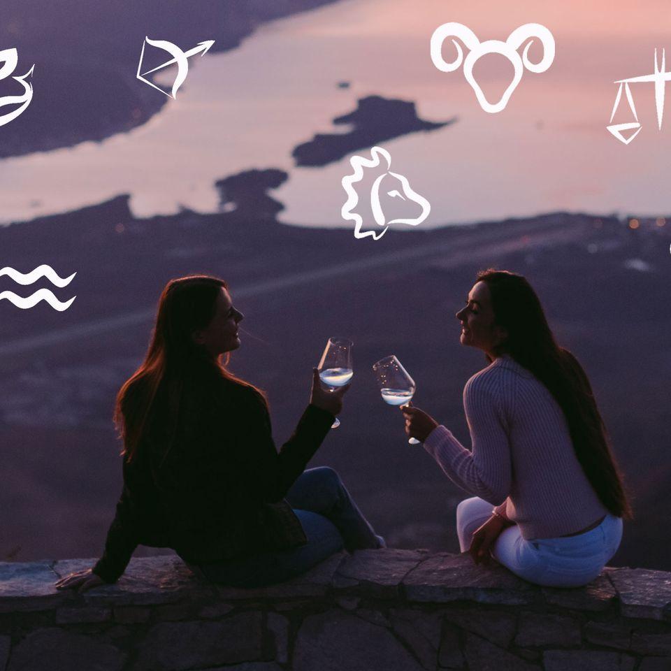 Gründe, warum jeder einen Wassermann im Leben braucht: Zwei Frauen auf einer Burg am See mit Weißwein
