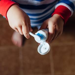 Zähneputzen lernen: Kind hält Zahnbürste und Zahnpasta