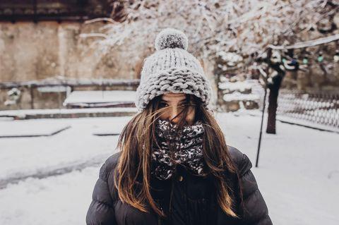 Tipps bei Kälte: Eine dick eingepackte Frau mit Mütze im Schnee