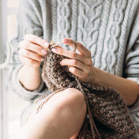 Selber stricken: Die besten Pullover: Frau im Strickpulli sitzt auf einem Stuhl und strickt