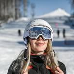 Hautpflege beim Skifahren: Frau mit Skihelm und Skibrille auf der Skipiste