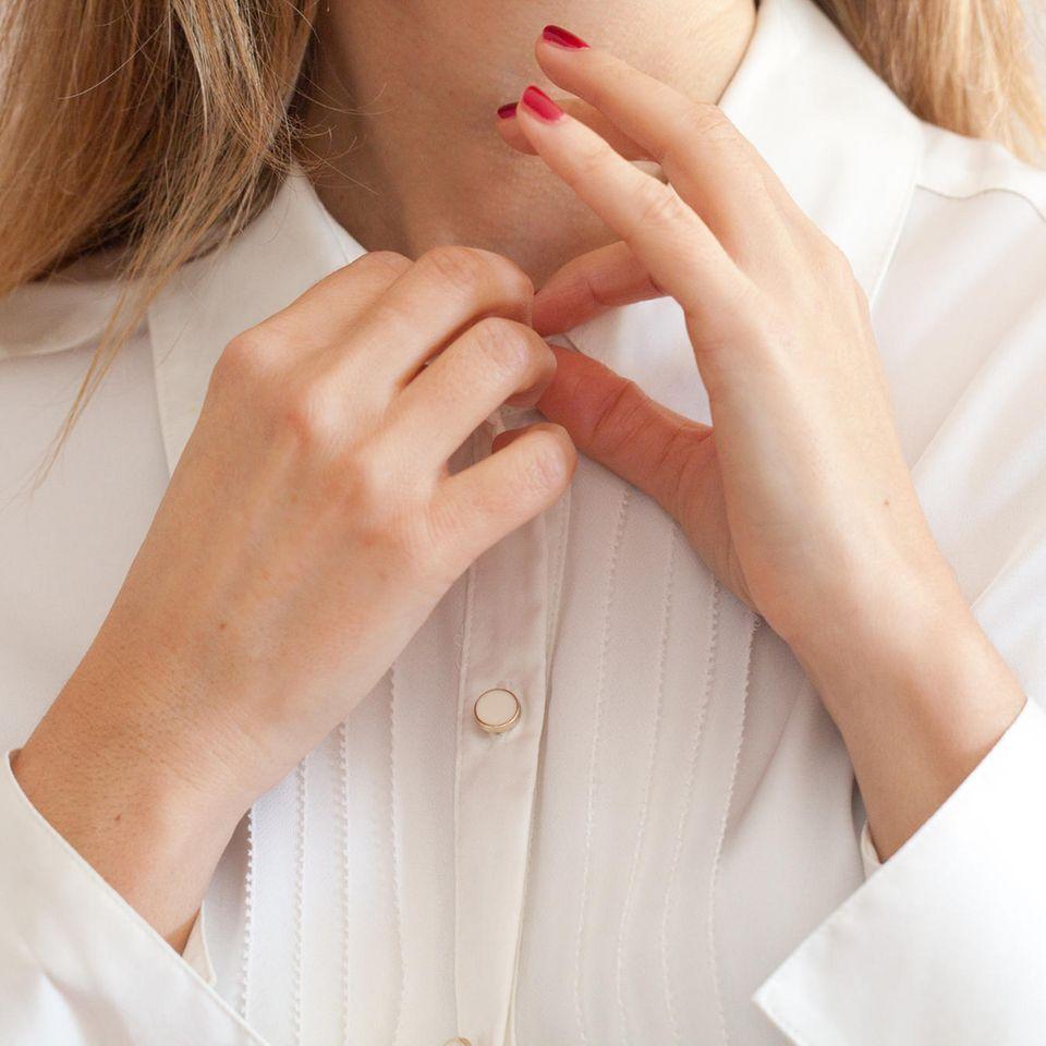 Perfektionismus: Frau knöpft ihr Hemd zu
