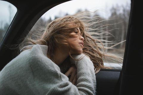 Wann muss ich mein Leben ändern? Eine Frau im Auto bei offenem Fenster