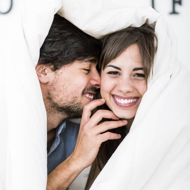Was ist das Geheimnis glücklicher Beziehungen? Ein glückliches Paar unter einer Bettdecke