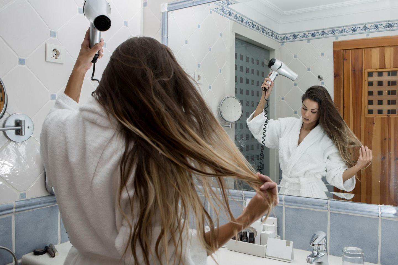 Föhn-Fehler: Frau, die sich die Haare föhnt