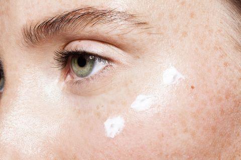 Augenpflege: Frau mit Augencreme unter dem Auge