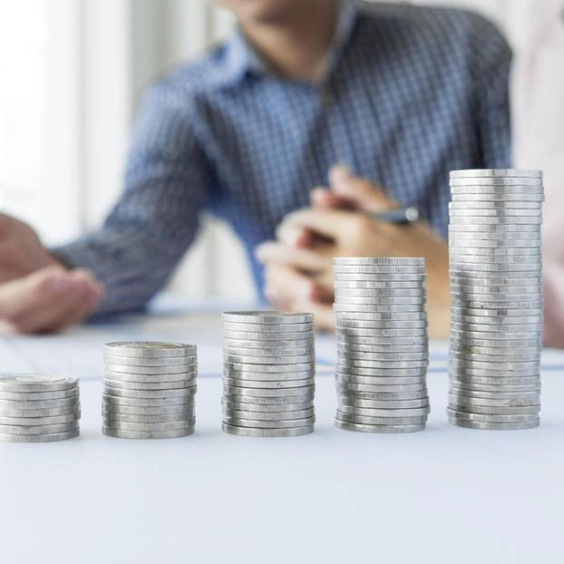 Gehaltserhöhung: Gestapelte Geldmünzen auf Schreibtisch