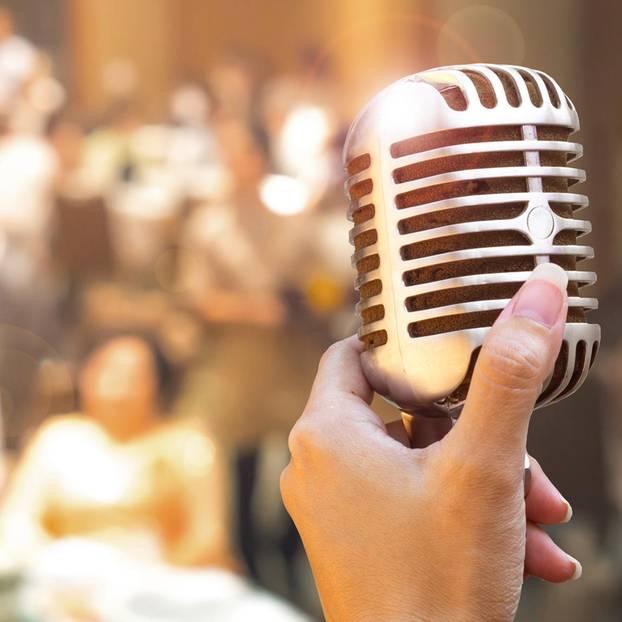 Trauzeugenrede: Eine Frau am Mikro auf einer Hochzeit