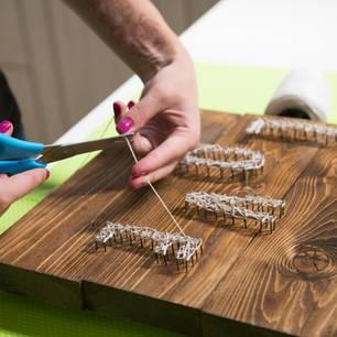 Basteln mit Holz: Frau schneidet Buchstaben auf Holz