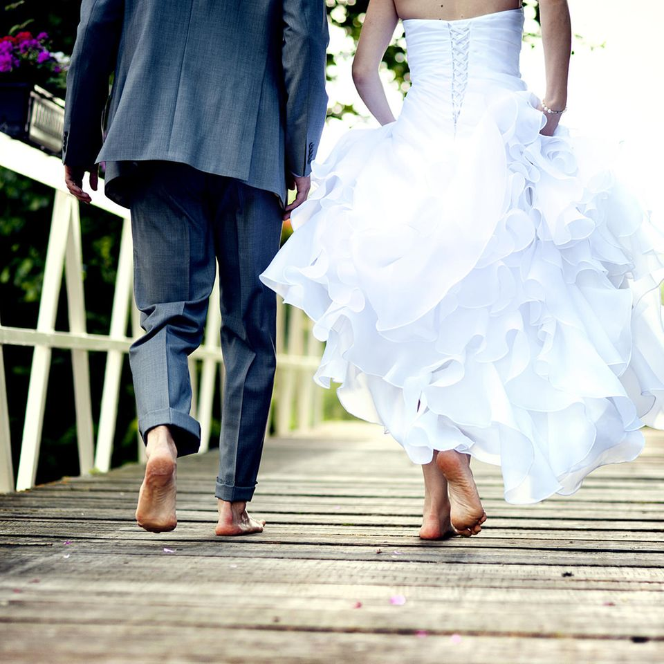 Wie ändern sich Menschen nach einem Jahr Ehe? Brautpaar von hinten, barfuß