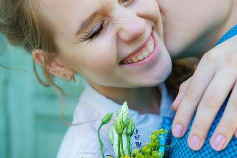 Wie erkenne ich einen lieben Kerl? Eine fröhliche Frau umarmt einen Mann, der ihr Blümchen mitgebracht hat