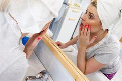 Hexenhaar: Frau betrachtet sich im Spiegel