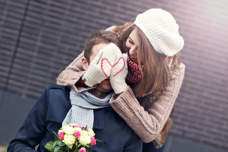 Liebeserklärung: Frau mit Herzchen-Handschuhen hält Mann von hinten die Augen zu