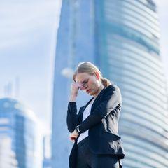 Angst vor der Arbeit – das solltest du tun: Gestresste Frau steht vor Bürogebäuden und fasst sich an den Kopf