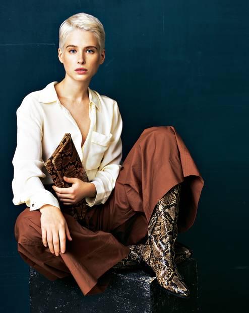 Reptilienprint: Frau in cremefarbener Bluse, brauner Stoffhose und Stiefel mit Schlangenprint