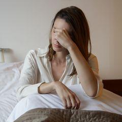 Niedriger Blutdruck: Hausmittel: Müde Frau im Bett
