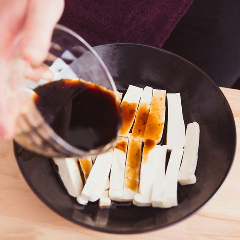 Tofu marinieren: 3 leckere Variationen: Schale mit geschnittenem Tofu über die Sojasauce gegossen wird